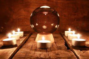 boule de cristal pour prédire le sort et l'action surnaturelle sur la table de l'ancien acajou avec des bougies et des cartes